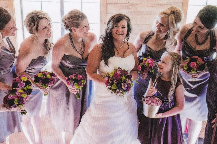 Bride surrounded by smiling bridesmaids holding matching wedding bouquets