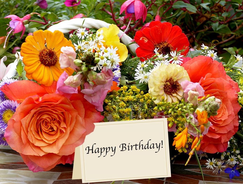 Birthday bouquet with many different flower types and a happy birthday card