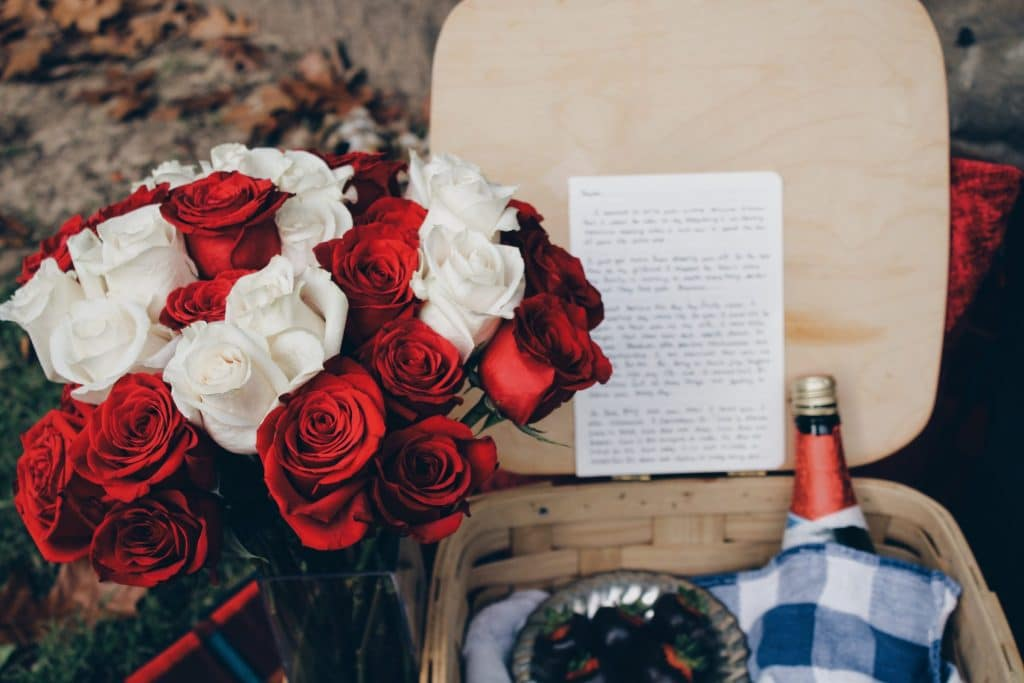 Bouquet of red and white roses and picnic basket with bottle of wine and note