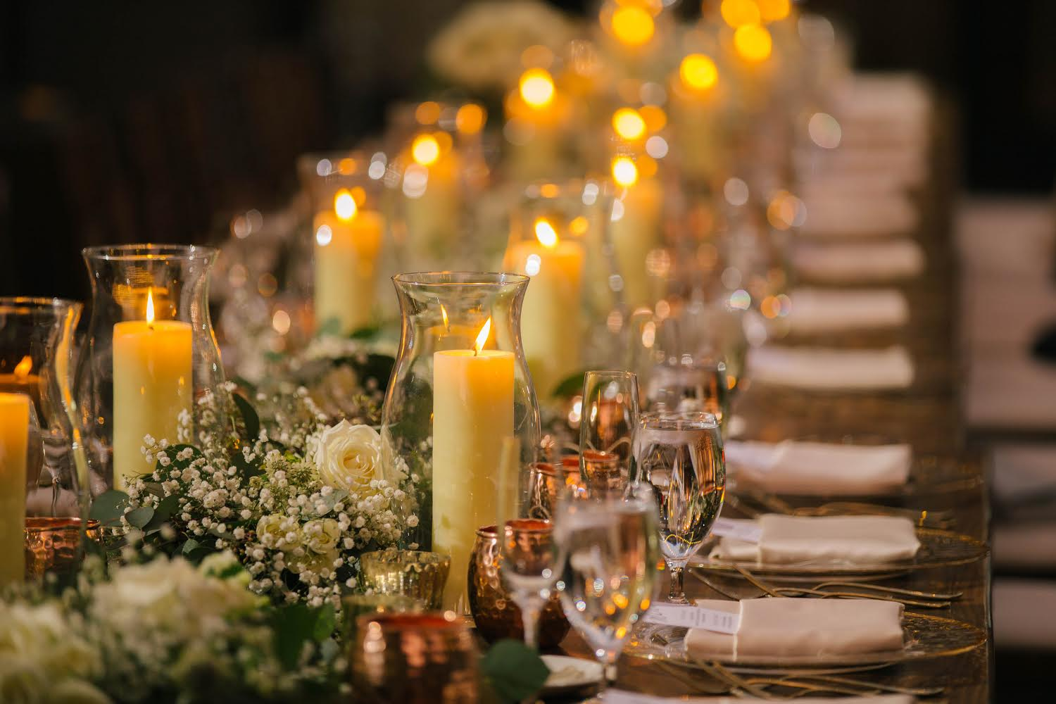 long line of floral arrangement and candles on wedding table